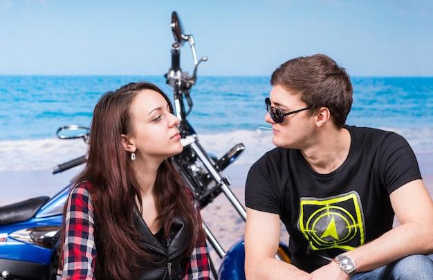 오토바이와 함께 아름 다운 해변에 앉아있는 동안 서로 마주하는 심각한 젊은 부부를 닫습니다.