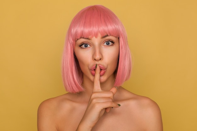 Close-up of serious young pretty woman with short pink hair keeping forefinger on her mouth while looking excitedly , asking to keep secret, isolated over mustard wall
