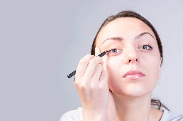 Закройте вверх серьезной молодой женщины, применяя макияж подводки для глаз на ее правый глаз, серьезно глядя в камеру, сняв на сером фоне.