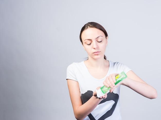 コピースペースで明るい灰色の背景の綿に液体洗顔料を置く深刻な若い女性を閉じます。