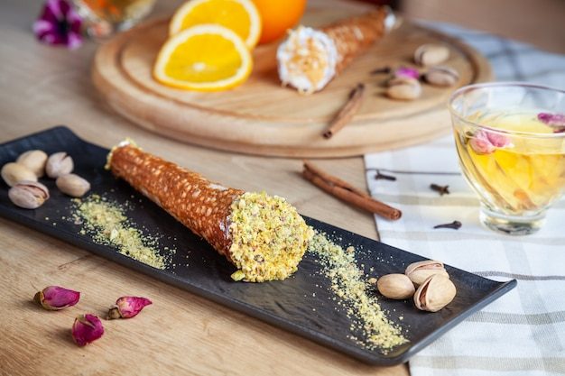 Close up on served cannoli with orange. italian cuisine pastry. traditional italian dessert with ricotta cheese. selective focus. sicilian sweets. copy space for design. food photo, horizontal