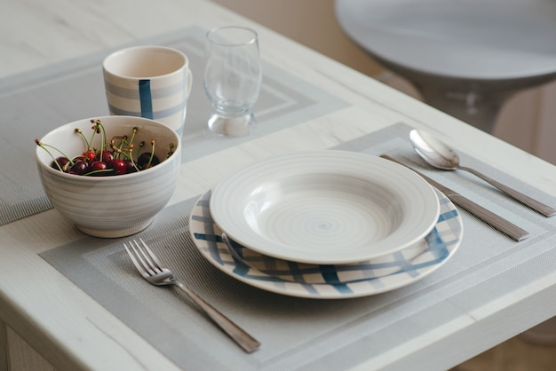 Close-up of served dinner plate, knife, spoon and fork, cup and a glass and a bowl of cherries on the dining table