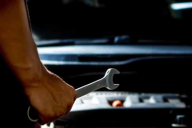 Close up, service car is people are repair a car use hand a wrench and a screwdriver to work.