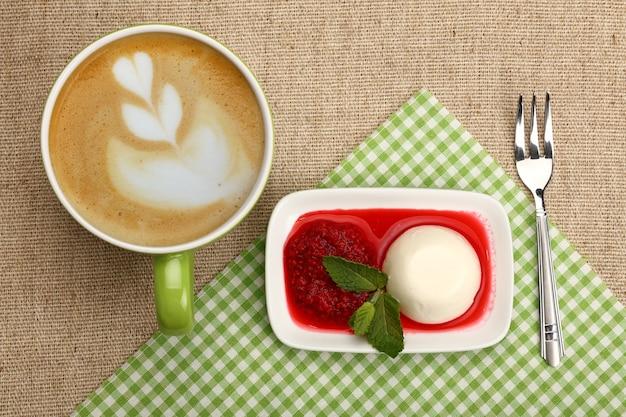 Крупный план, где подают традиционный итальянский десерт панна котта с малиновым джемом и чашкой капучино, вид сверху, прямо над