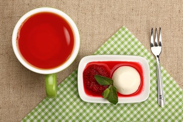 Крупным планом подают традиционный итальянский десерт панна котта с малиновым джемом и чашкой красного черного чая