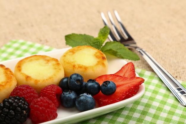 Крупным планом порция десерта из европейских творожных блинчиков с фруктами на столе, высокий угол обзора, личная перспектива