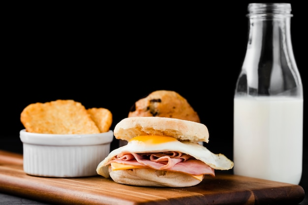 Close-up set benedict egg sandwich next to milk bottle