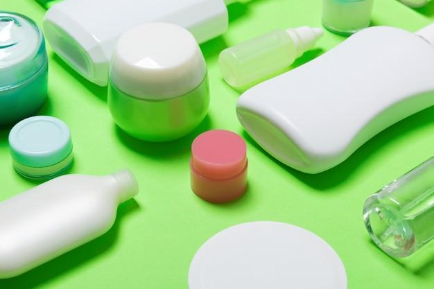 Крупным планом набор разных размеров бутылок и банок для косметических продуктов на зеленом фоне. уход за лицом и телом copyspace