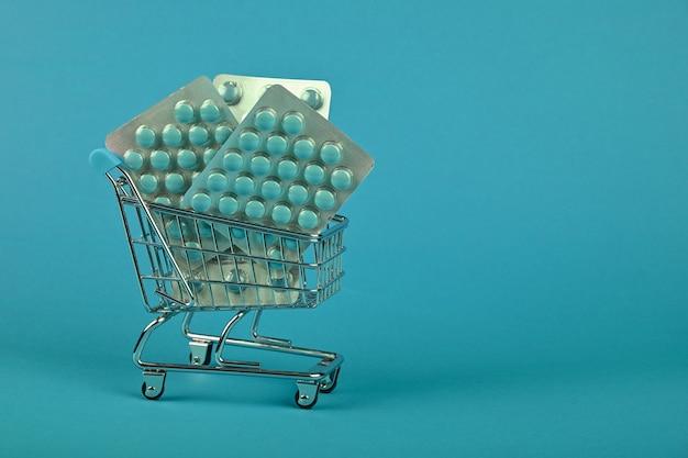 青い背景、オンライン薬注文配信の概念、ローアングルビュー上の小さなショッピングカートで錠剤のいくつかの異なるブリスターパックを閉じる
