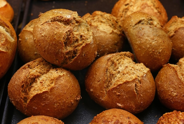Close up several fresh wheat bread buns with seeds on retail display of bakery store, high angle view