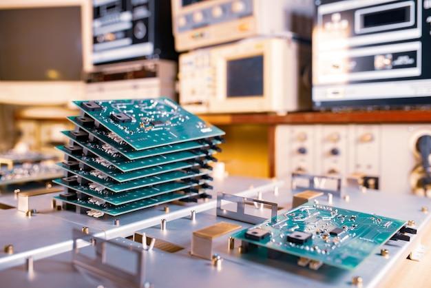 Крупным планом несколько рядов с компьютерными микрочипами лежат на столе на фоне компьютеров, бытовой и оргтехники. концепция устаревшей технологии прошлых лет