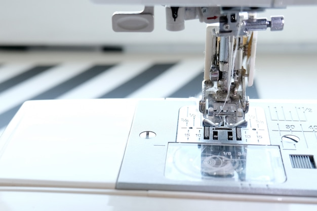 Close up sewing machine at tailor workplace. sew process. - needlework, craft, sewing and tailoring concept.