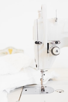 Close-up of sewing machine and white cloth