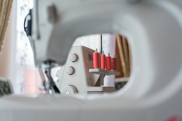 Close up of sewing machine with coils of coral thread