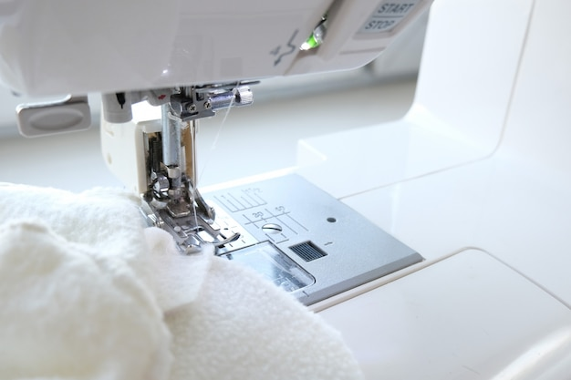 Close up sewing machine with white fabric textile at workplace. sew process. - needlework, craft, sewing and tailoring concept.