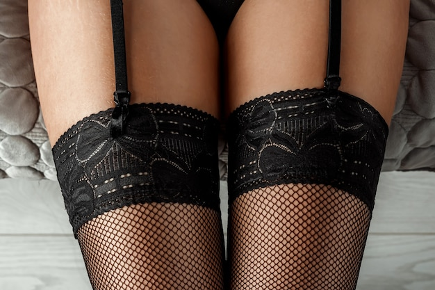 Close-up of sexy female legs in black stockings. perfect skin. sex life concept, role-playing games.