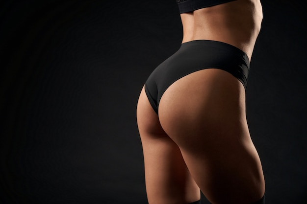 Close up of sexy incognito female model wearing sports black underwear standing, isolated on black studio background. back view of fit caucasian woman with perfect buttocks posing.