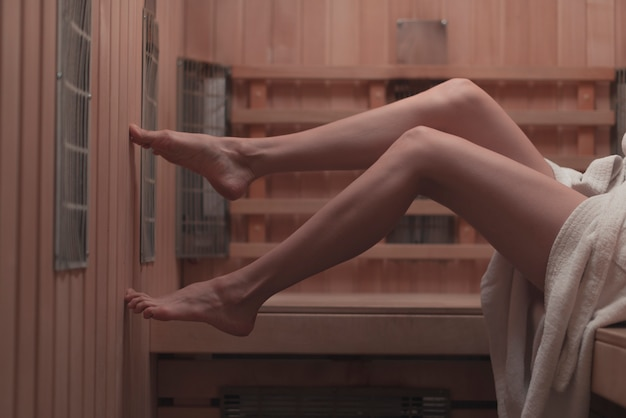 Close-up of sexy woman's feet on bench at sauna