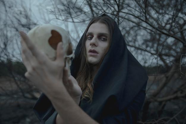 Close-up shakesprerian man holding a skull