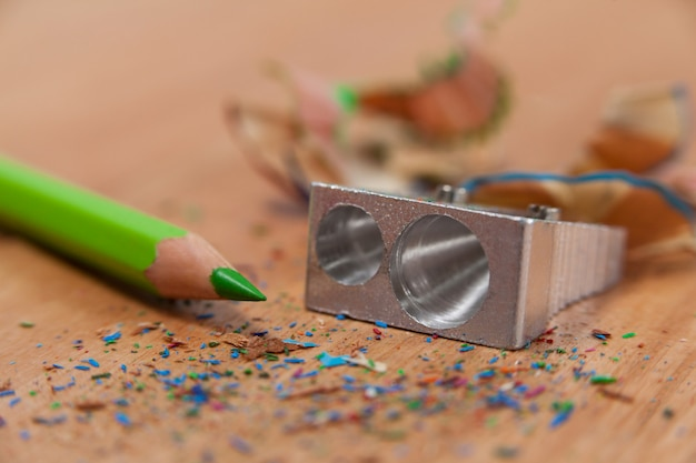Close-up of sharpener and colored pencil with shavings