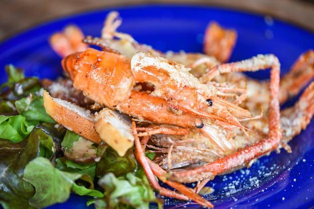 Закройте вверх тарелка морепродуктов моллюсков креветки креветки ужин еда приготовленные креветки на гриле с овощами и сыром