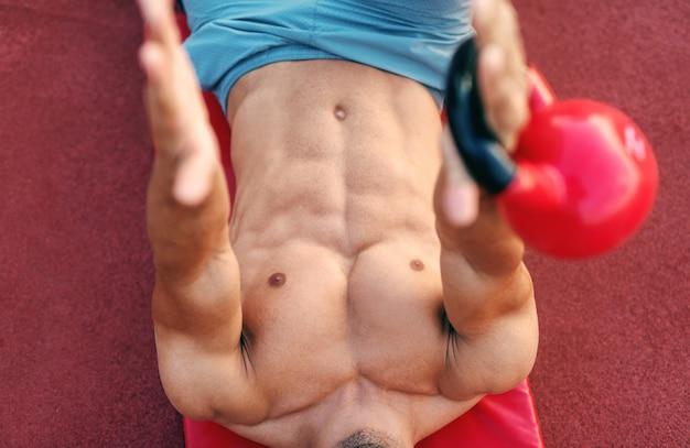 コートでマットの上に横たわると朝にケトルベルで演習を行う上半身裸の筋肉男を閉じます。屋外フィットネスの概念。