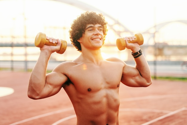 Close up of shirtless smiling man with curly hair lifting dumbbells while standing on court in the morning