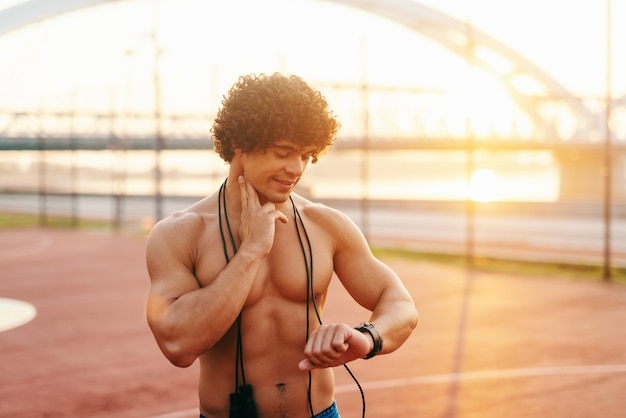 Close up of shirtless smiling sporty man checking heart beat after skipping rope