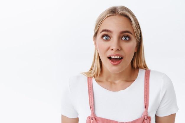 ピンクのオーバーオール、tシャツ、口を開けて魅了された青い目をしたクローズアップのショックを受けて感動したブロンドの女の子は、興味からあえぎながら白い背景に立って、驚くべきニュースを見つけました