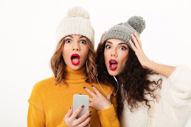 Close up shocked girls in sweaters and hats standing together with smartphone  over white wall