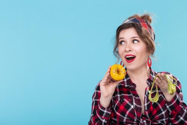 クローズアップは、巻尺を見て、コピースペースで青い背景にポーズをとってドーナツを手に持って驚いた若い美しい女性を驚かせた。有害な高カロリー食品の食事療法と拒絶反応。