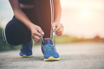 靴を閉じますジョギングの運動のために彼女の靴を結ぶ女性ランナー