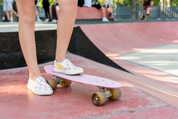 Close-up of shoes on pink skateboard