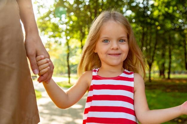 Съемка крупного плана довольно маленькой белокурой длинноволосой девочки ребенка в красочном платье, доверчиво держа руку молодой матери