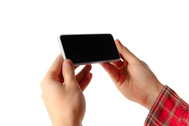 빈 화면 흰색 스튜디오 벽에 고립 된 모바일 스마트 폰을 사용 하여 젊은 백인 남자의 촬영을 닫습니다. 현대 기술, 가제트, 기술, 감정, 광고의 개념. copyspace.