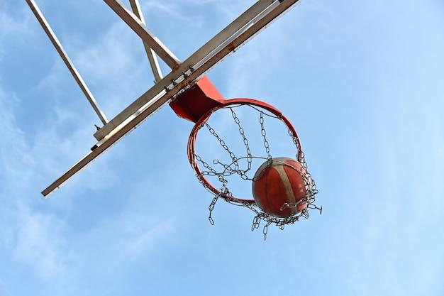 오렌지 컬러 농구 공을 야외 코트에서 바구니에 쏘는 것을 닫습니다, 낮은 각도보기, 바로 아래