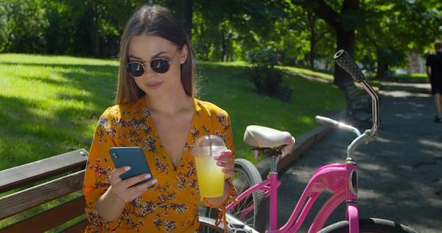 クローズアップ撮影。自転車で魅力的な若い女性の肖像画は、スマートフォンを使用し、公園のベンチでレモネードを飲んでいます。ファッショナブルな若い女性は、アクティブなライフスタイルとスポーツを持っています。