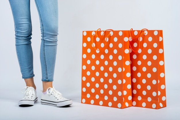 Close-up shopping bags mock-up near woman legs