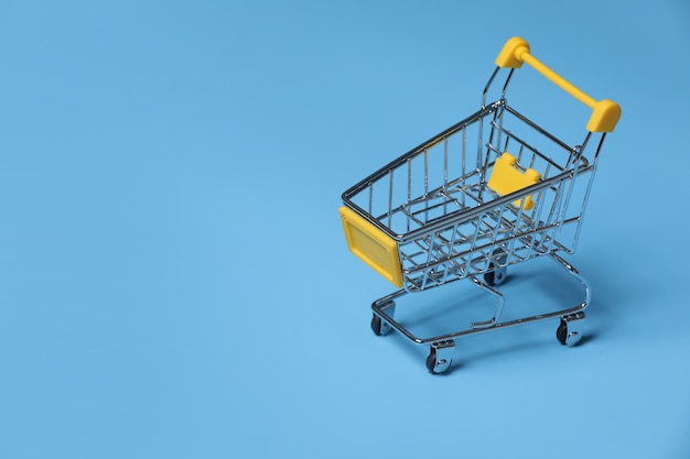 Close-up of shopping trolley on blue background with some copy space. empty shopping cart on blue background