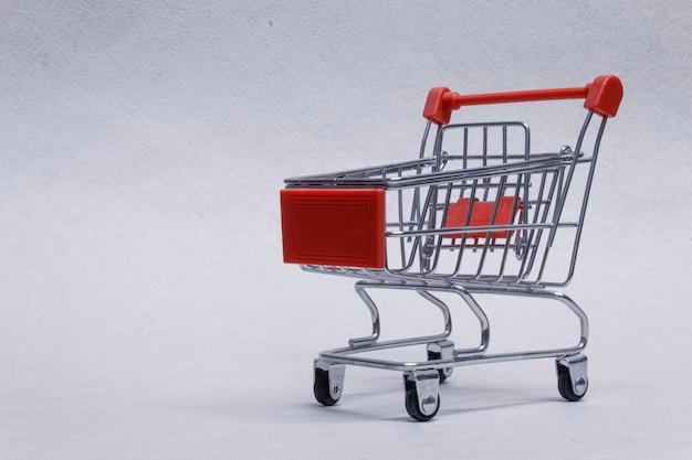 Close-up of shopping trolley on light background.
