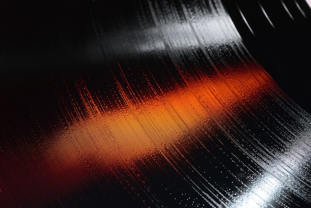 Close-up shot of 12-inch lp vinyl record groove with white and orange lights.