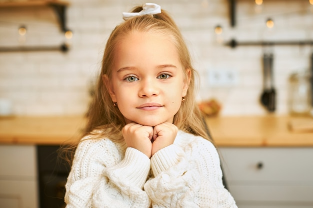 Close up shot of adorable little girl with green eyes and long loose hair holding hands under her chin with smile posing in kitchen