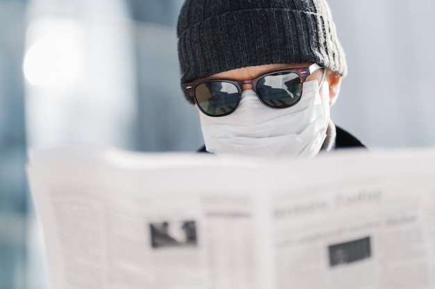 Close up shot of adult man wears sunglasses, hat and sterile medical mask, reads newspaper, finds out news about situation in world, coronavirus spread, poses outdoor against blurred background