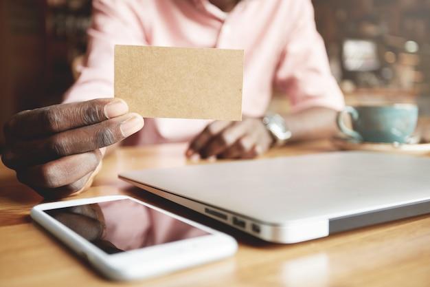 Immagine ravvicinata di lavoratore aziendale africano che mostra carta pergamena vuota