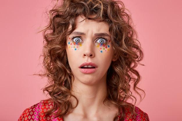 Inquadratura ravvicinata di una giovane donna sbalordita con gli occhi spalancati, guardando, isolato, indossando abiti a strisce rosa e arancioni