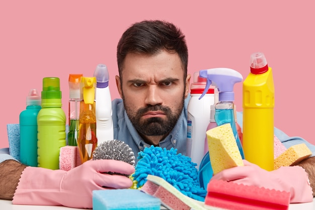 Close up shot of angry unshaven man embraces many bottles of detergent and sponges, wears rubber protective gloves