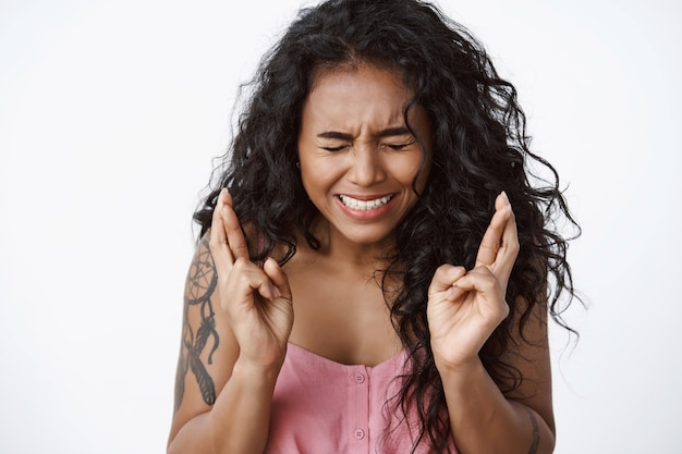 Close-up shot anxious and worried curly-haired female with tattoos, squinting, clench teeth nervously, cross fingers good luck, anticipating important thing, praying standing white wall
