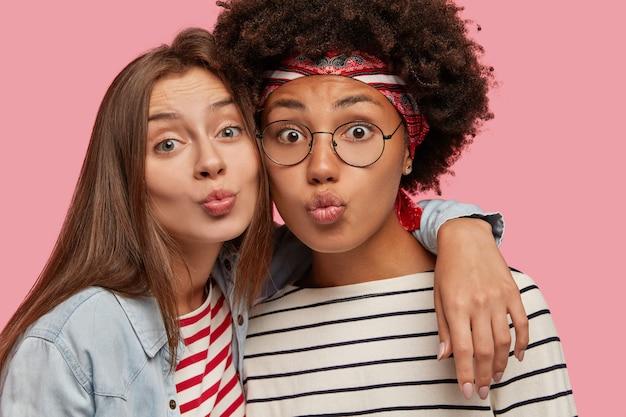 Immagine ravvicinata di attraenti femmine di razza mista bella fanno una smorfia, labbra imbronciate come per baciare qualcuno