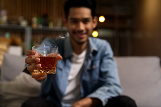 Close up shot of asian man holding glass of whiskey in night club restaurant.