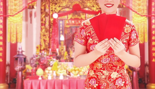Крупным планом выстрел азиатская женщина в платье китайской традиции cheongsam, держа красный конверт для дачи денег на фестивале китайского нового года в китайском храме